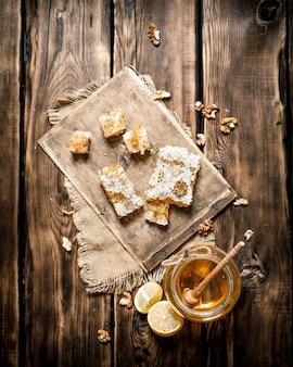 Sfondo di miele. miele naturale fette di limone e noci. sullo sfondo di legno.