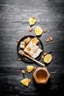 Sfondo di miele dolce miele naturale con limone su fondo rustico nero