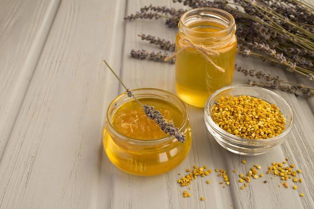 Miele e polline d'api sul legno grigio