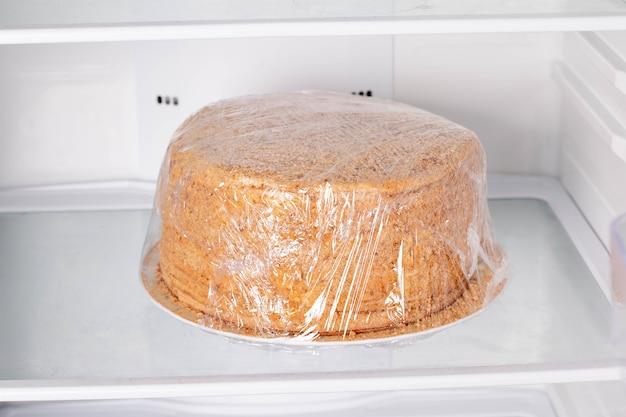 Torta al miele medovik confezionata in pellicola trasparente in frigorifero. torta congelata