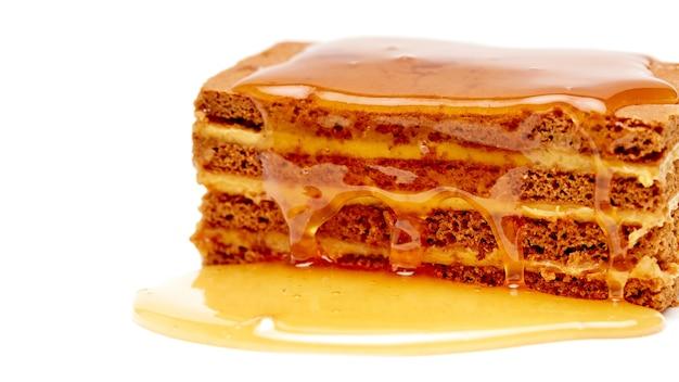 Torta al miele versata sopra con miele su uno sfondo bianco isolato con un posto dove copiare il testo