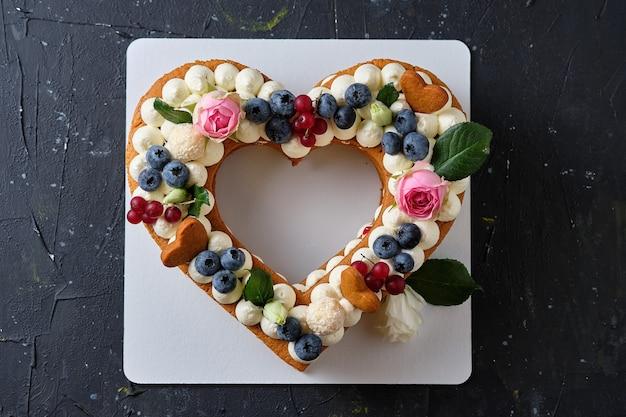 Torta al miele con mirtilli freschi, erbe aromatiche e crema di formaggio cremoso. dessert per una persona cara. torta di cuore.
