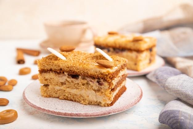 Torta al miele con crema di latte, caramello, mandorle e una tazza di caffè su uno sfondo di cemento bianco e tessuto di lino.