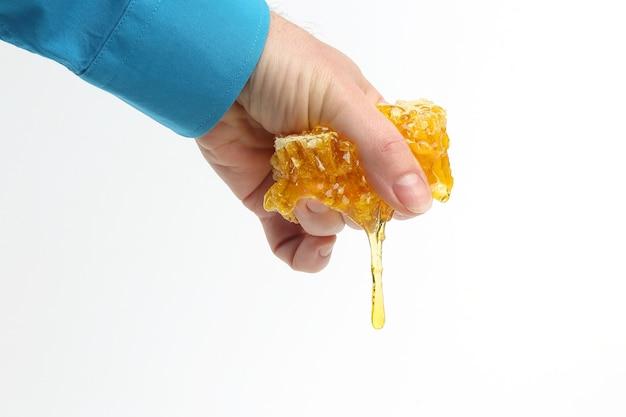 Pettine di miele grondante con mani umane su bianco