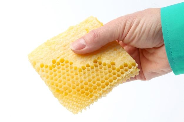 Favo di miele in mano su sfondo bianco. cibo sano