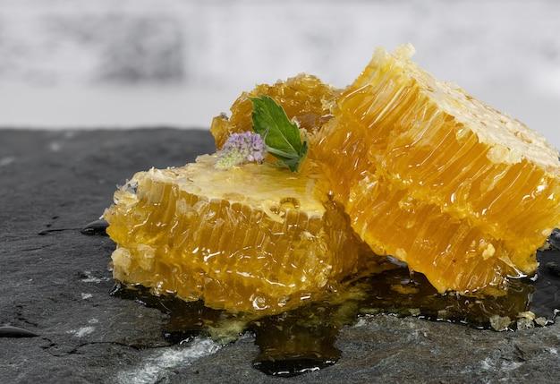 Favi di miele tagliati a pezzi con un fiore di menta lilla su una pietra di granito grigio