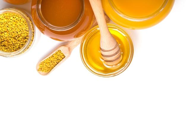 Mestolo di miele e miele in barattolo su sfondo bianco
