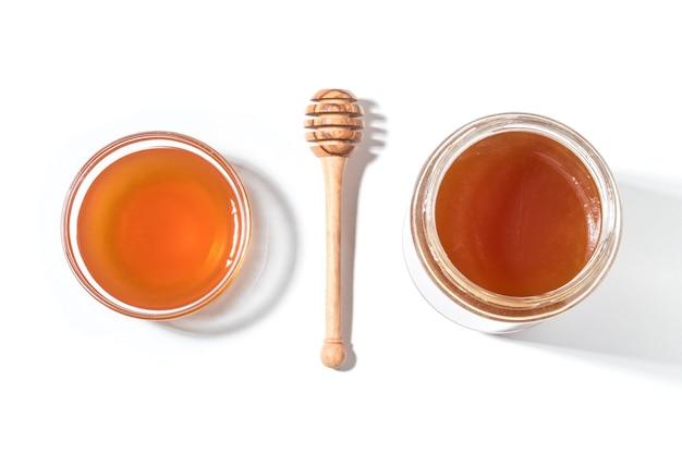 Mestolo di miele e miele in vaso sulla superficie bianca.