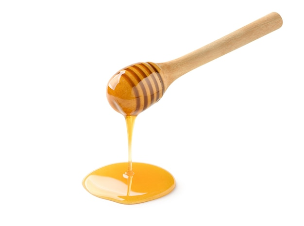 Miele che gocciola dal mestolo di miele isolato su bianco