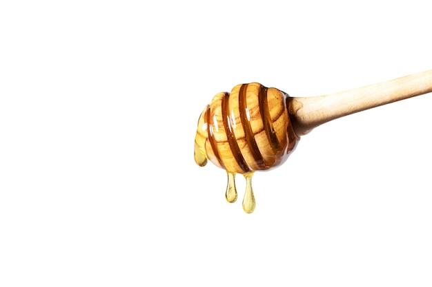 Miele che gocciola dal mestolo di miele sulla superficie bianca.