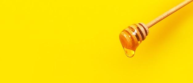 Miele che gocciola dal mestolo di miele su sfondo giallo. miele denso che si immerge dal cucchiaio di legno del miele. concetto di dieta e cibo sano