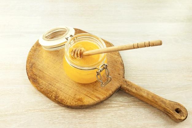 Miele che gocciola da un mestolo di legno sul vecchio tagliere