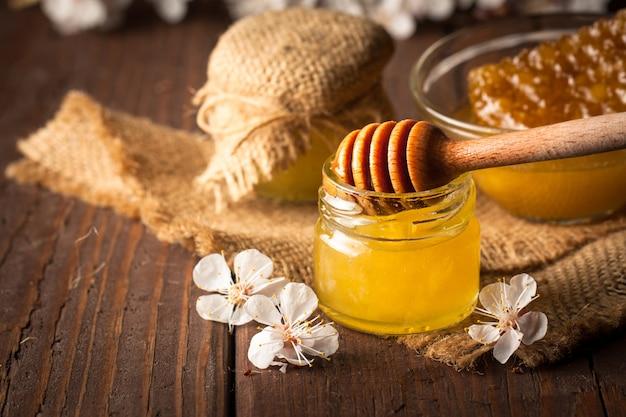Miele gocciolante da un mestolo di legno miele