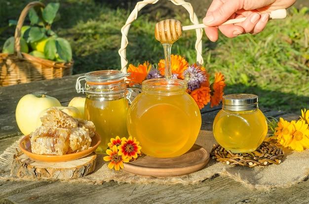 Il miele che gocciola in un barattolo su un tavolo di legno alla luce del sole