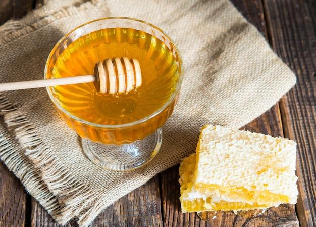 Il miele gocciola da un mestolo di miele in una bella ciotola di vetro. avvicinamento. miele e favi organici sani e spessi.