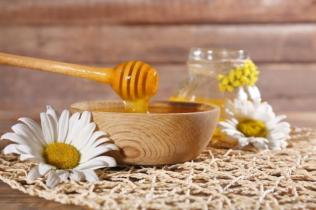 Miele e fiori sulla stuoia di vimini