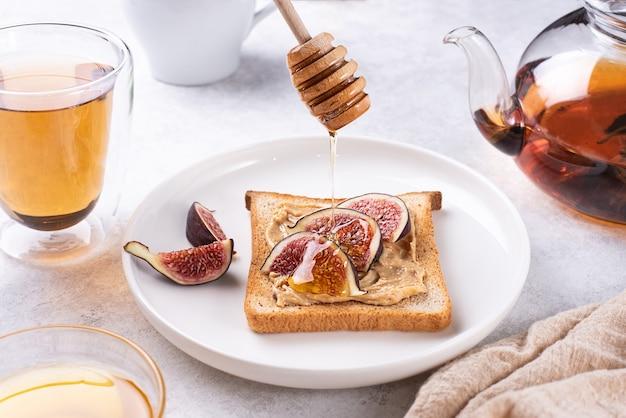 Miele che scorre verso il basso per tostare con burro di arachidi e fette di fichi su un piatto su un piatto bianco, colazione sana, primo piano.