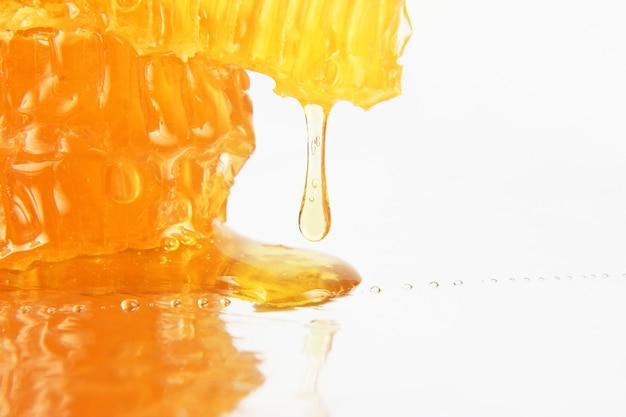 Miele che scorre dai favi su uno sfondo chiaro