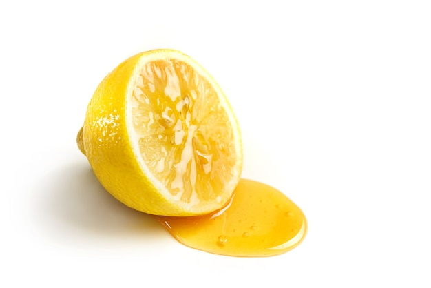 Il miele scorre da una glassa di limone. mezzo limone con miele su un piatto bianco con spazio di copia.