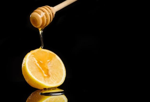 Il miele scorre da un cucchiaio a un limone che giace su uno sfondo nero con spazio di copia.