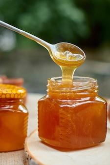 Il miele scorre da un cucchiaio di acciaio in un barattolo di vetro