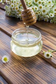 Miele nel barattolo di vetro e camomille sullo sfondo di legno marrone. posizione verticale.