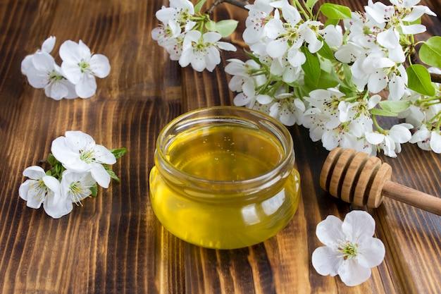 Miele nel barattolo di vetro e nei rami degli alberi in fiore