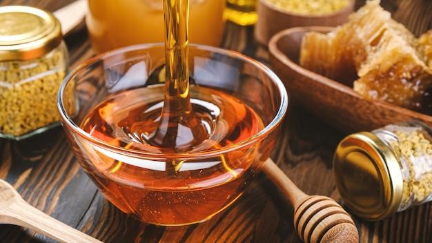 Miele in un barattolo di vetro con mestolo di miele su sfondo di legno con favo e propoli, sciroppo di zucchero liquido, nettare di fiori
