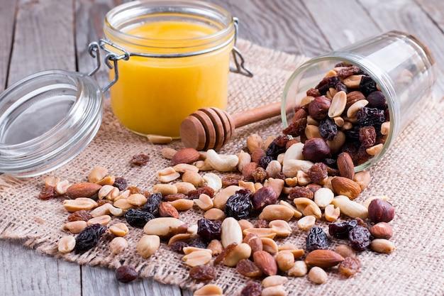Miele in barattolo di vetro con noci su legno rustico