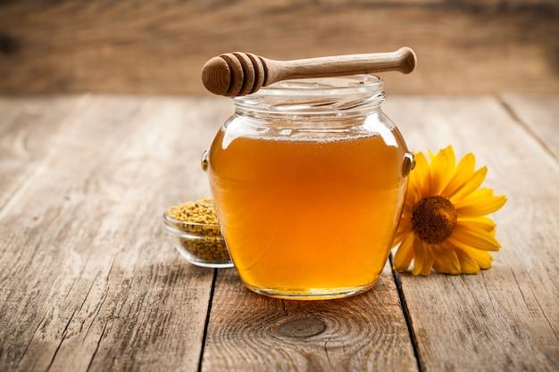 Miele in barattolo di vetro su fondo di legno