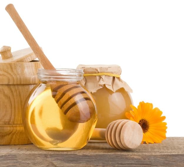 Miele in vaso di vetro e legno isolato su bianco