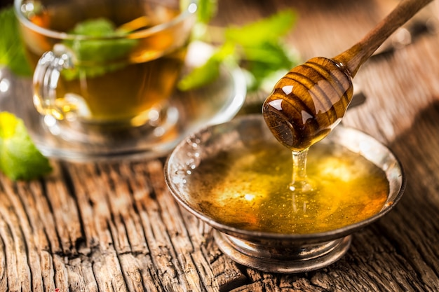 Tesoro. miele e mestolo di miele su tavola in rovere rustico. tisana calda in sottofondo.
