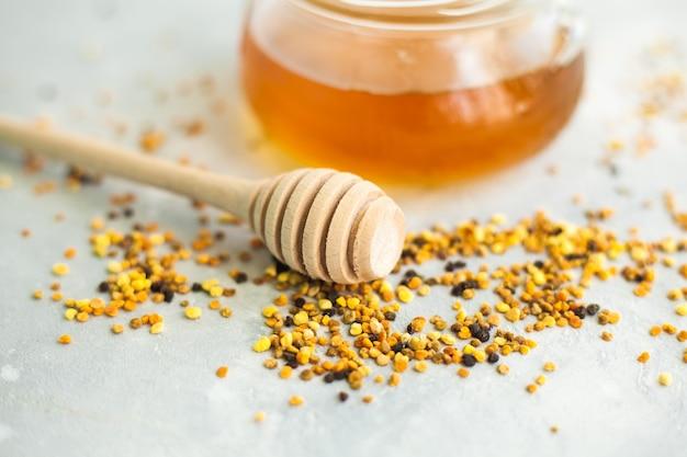 Miele e cucchiaio di miele su uno sfondo chiaro.