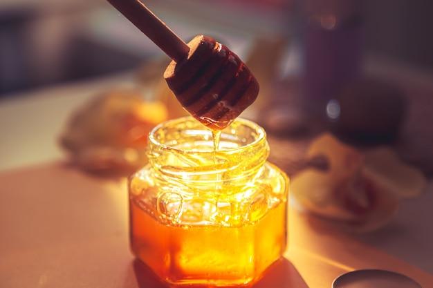 Il miele viene versato nel barattolo. concetto di cura della stazione termale. cura della pelle naturale a casa. sfondo sfocato. bella luce.
