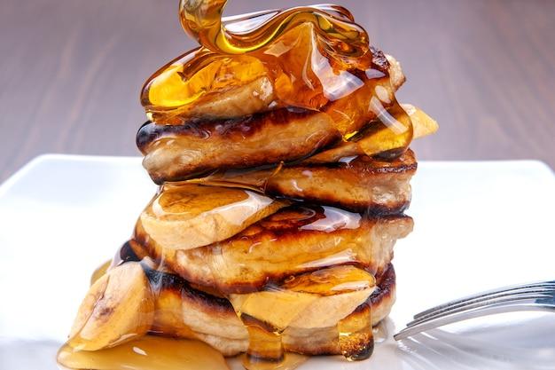 Il miele sta versando sulle frittelle con la banana su fondo di legno