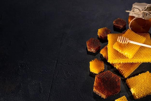 Miele in un barattolo e un favo. su uno sfondo di legno nero. spazio libero per il testo. vista dall'alto.