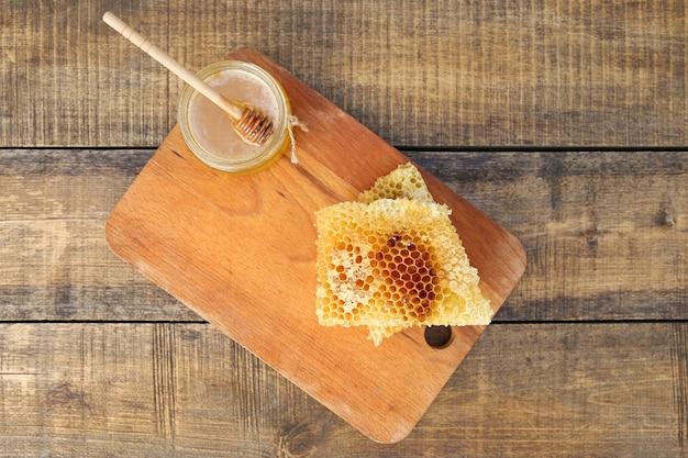 Miele in un barattolo e nido d'ape su un vecchio fondo di legno. vista dall'alto.