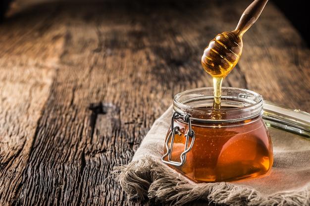 Barattolo di miele con mestolo sul vecchio tavolo in legno.