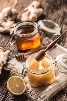 Miele in vasetti e mestolo su tavola in rovere rustico.