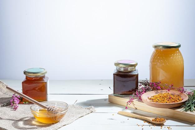 Vasetti di miele con bastoncini di miele e fiori