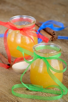 Miele in barattoli su un tavolo di legno accanto ai bastoncini di cannella e un cucchiaio