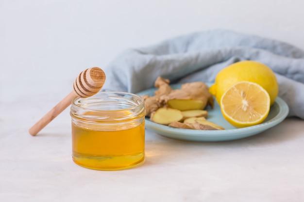 Miele, limone, zenzero su un tavolo luminoso. rimedi popolari per il trattamento del raffreddore. medicina fredda biologica. rimedi naturali per il raffreddore