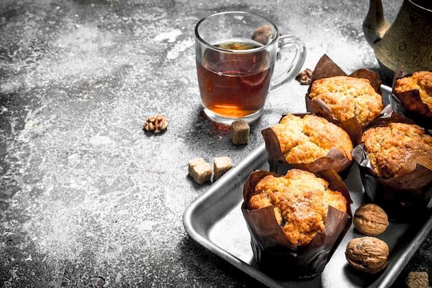 Muffin al miele con tè profumato. su un tavolo rustico.