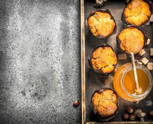 Muffin al miele con noci su un vecchio vassoio. su un tavolo rustico.
