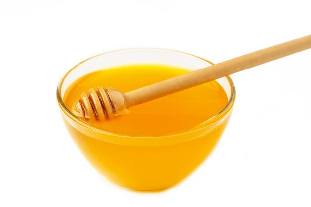Pentola di miele e mestolo isolati su sfondo bianco come elemento di design della confezione