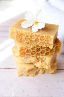 Il sapone al miele è posto sull'asciugamano sul tavolo di legno.