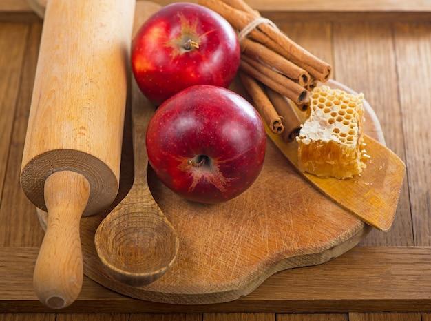 Cucchiaio di miele, vasetto di miele, mele e cannella su una superficie di legno in stile rustico