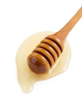 Miele e bastone isolati su bianco
