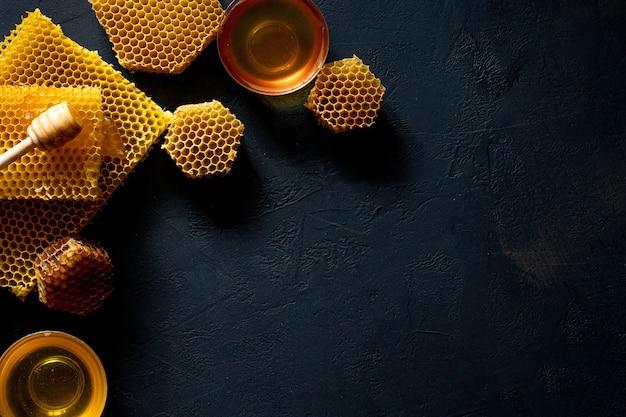 Miele con favo sulla tavola nera, vista dall'alto. spazio per il testo.