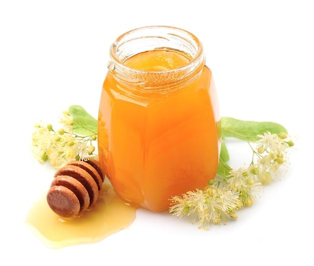 Miele con fiori di tiglio isolatewd su bianco.